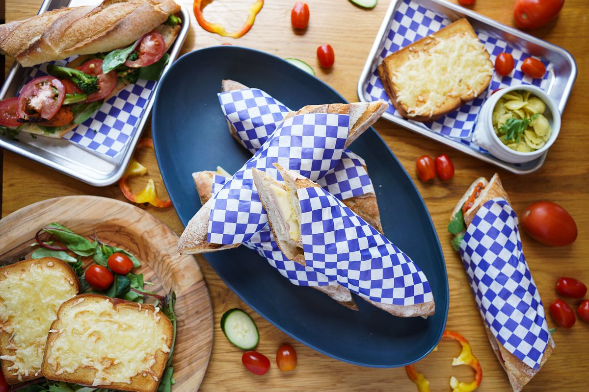 A table of plates and trays filled with French sandwiches wrapped in blue and white checked paper.