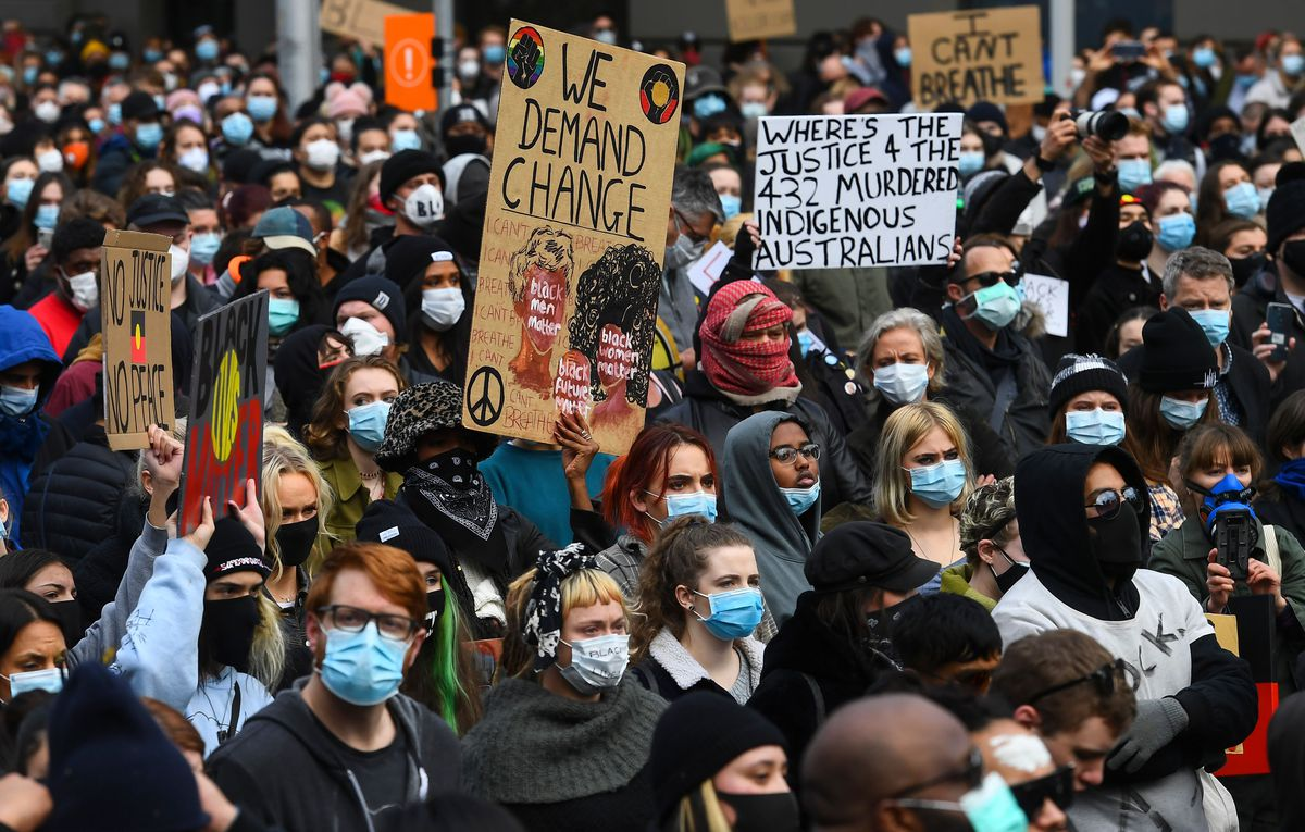 A multitude of different people are masked and shoulder to shoulder. Many hold on to signs; one reads: