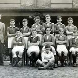 Leslie Norris, seen above when he was a 28-year-old teacher at Grass Royal School in Yevil, England, poses with the school football (soccer) team, which he coached.
