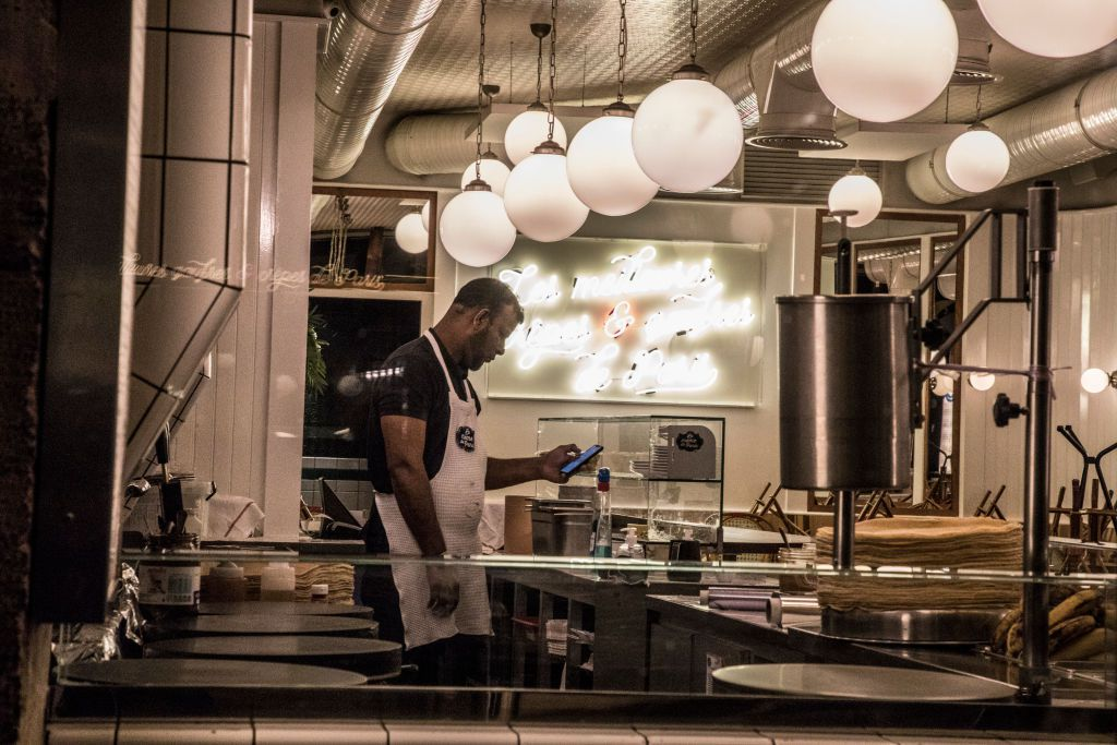 A chef holds a phone in a kitchen at night in a Paris restaurant
