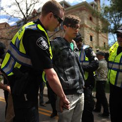 Colorado University Senior Jonathan Edwards is patted down for transportation after being arrested for trespassing on the Norlin Quad that is closed to crackdown on pro-marijuana protesters on 4-20-12 at the school in Boulder, Colorado, Friday, April 20, 2012. A block-long line of protesters marched onto the University of Colorado, testing the school's determination to push the annual April 20 marijuana celebration off campus.