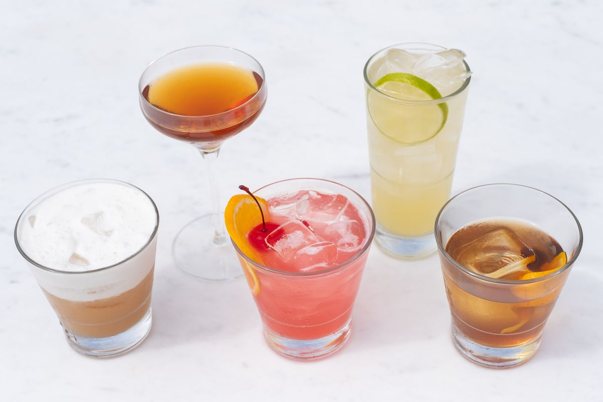 Five cocktails on a white surface