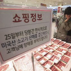 """A South Korean woman watches Australian beef on the shelves at a Lotte Mart store in Seoul, South Korea, Wednesday, April 25, 2012. Two major South Korean retailers, including Lotte Mart,  suspended sales of U.S. beef Wednesday following the discovery of mad cow disease in a U.S. dairy cow. Reaction elsewhere in Asia was muted with Japan saying there's no reason to restrict imports. The letters on a card read """" Starting from the 25th, we will temporarily stop the sales of the US beef. Thank you for your understanding""""."""