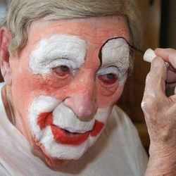 """In this March 29, 2012, photo, Floyd """"Creeky"""" Creekmore puts on his makeup before a visit with children at a circus in Billings, Mont. Guinness World Records has anointed the world's oldest performing clown, and it's none other than Creekmore, a former Montana rancher who's been donning the big nose and bright makeup for almost eight decades."""