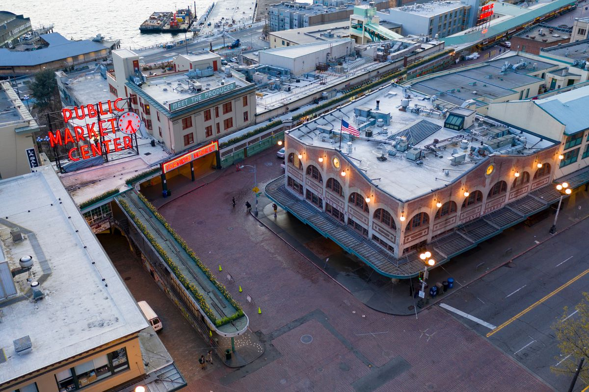 A bird's eye view of an empty Pike Place Market on a cloudy morning, with the famed neon sign shown to the left