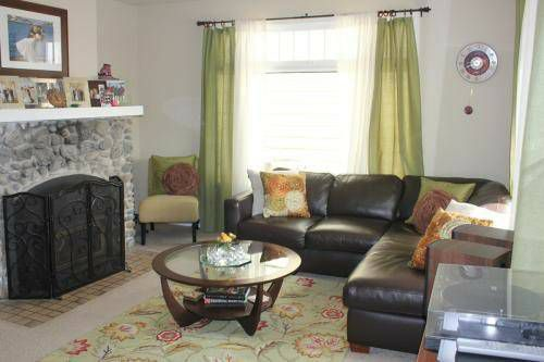A living room with a stone fireplace and a leather, corner sectional