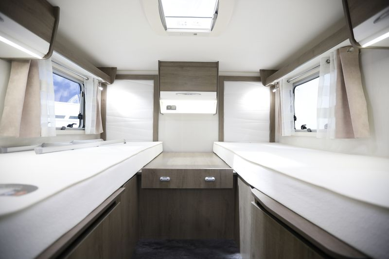 The interior of a motorhome with white beds on either side of a center table. Windows are above the beds.