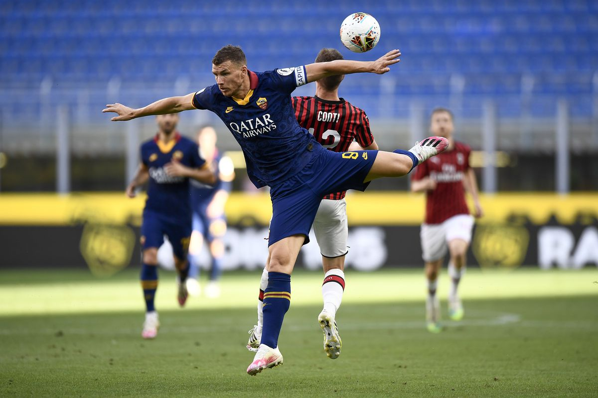 Edin Dzeko (L) of AS Roma competes for a header with Andrea...