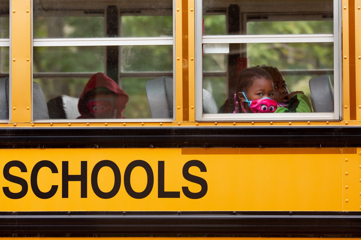 Close-up from outside a yellow school bus shows three young students wearing colorful masks sitting in two rows.