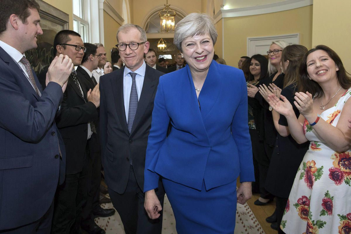 Britain's Prime Minister Theresa May and her husband Philip are applauded by staff as they return to 10 Downing Street, after seeking permission from Queen Elizabeth to form a new government, in London, Friday, June 9, 2017. May struck a deal in principle