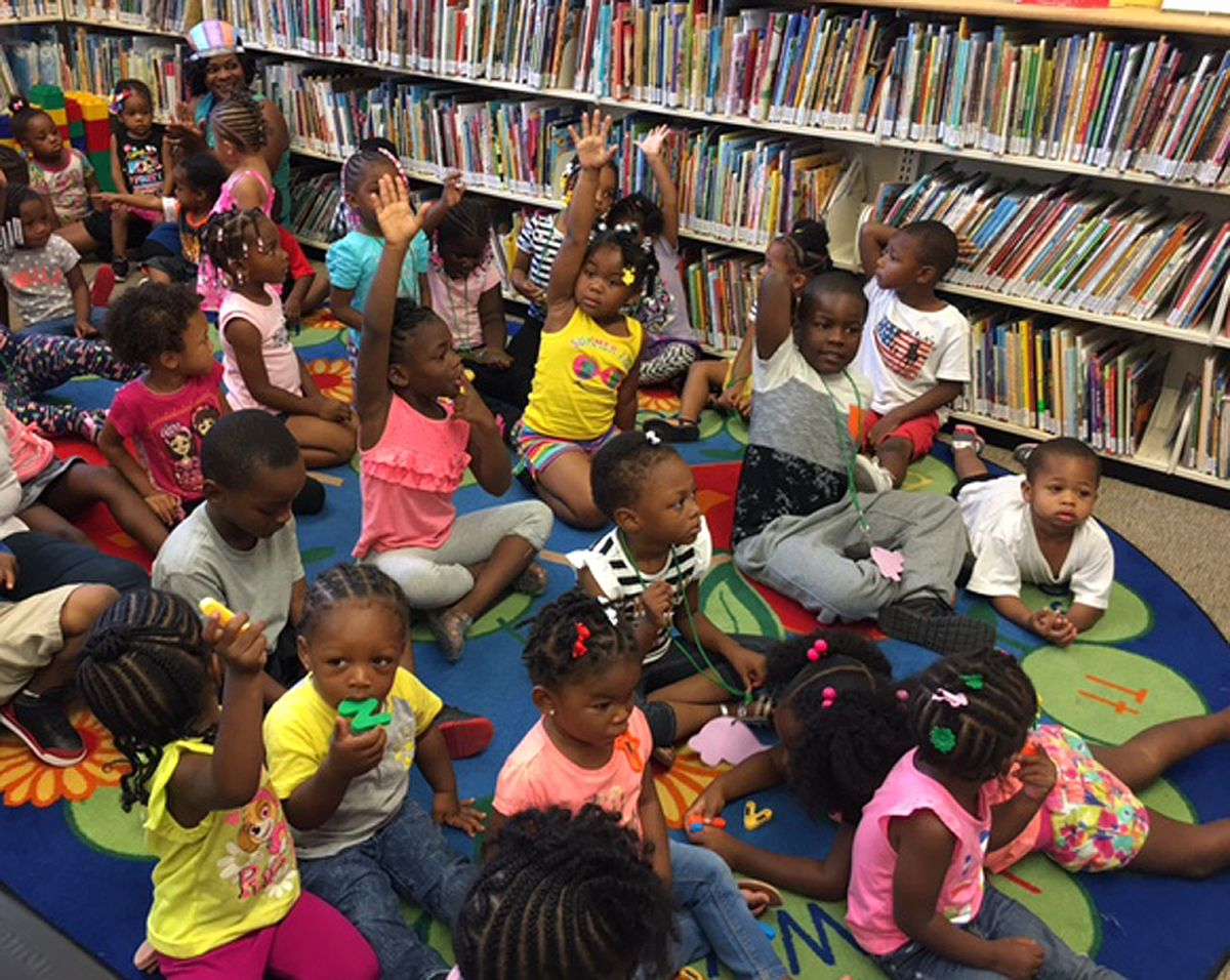 Children fill a cramped room at the current Altgeld Chicago Public LIbrary branch in August 2016 to listen to Mayor Rahm Emanuel read. The mayor and other officials were there to announce that a new, larger library is headed to the housing development.