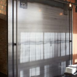 Massive sliding metal doors separate the private dining area from the restaurant