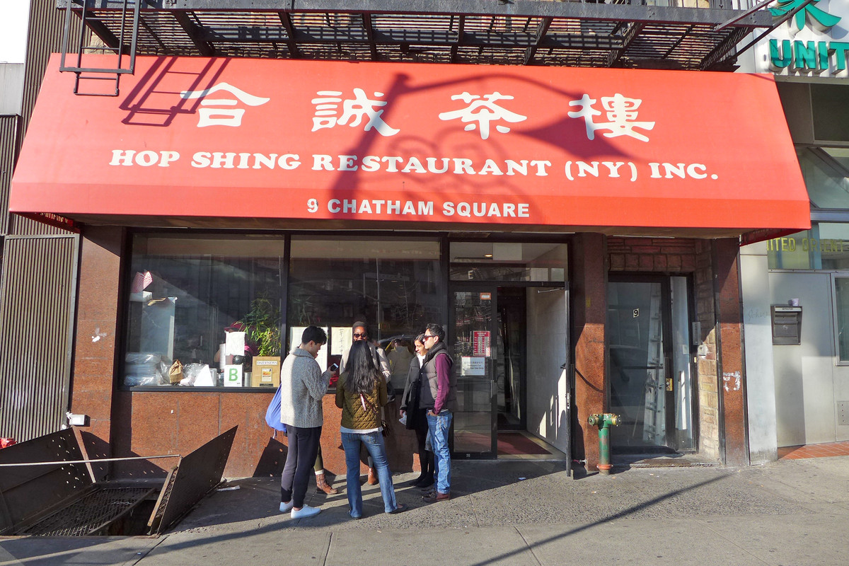 Four people clustered outside of the front of a restaurant with a big red awning that says Hop Shing Restaurant (NY) Inc and lists the restaurant's address