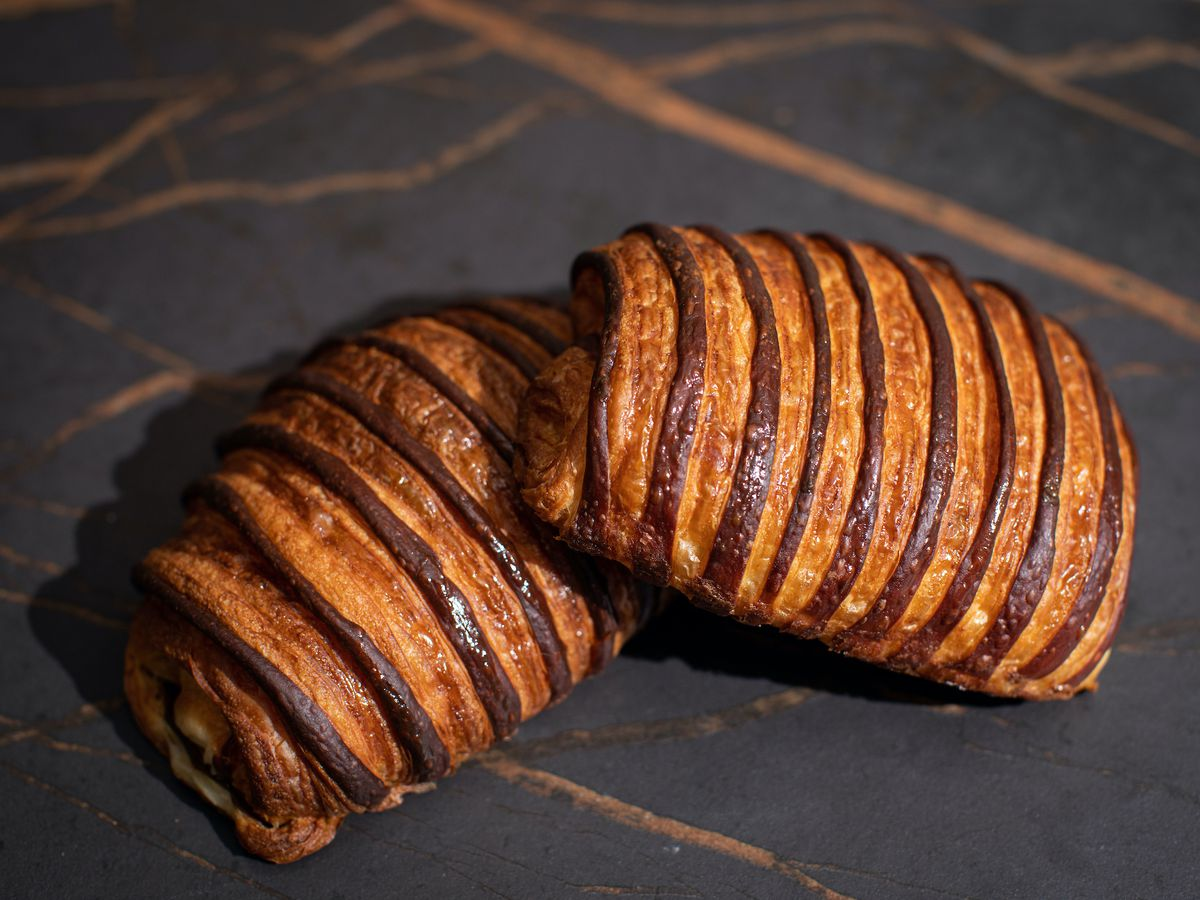 Two chocolate croissants with alternating layers of brown and dark brown dough stacked partially on top of each other on a dark grey surface.