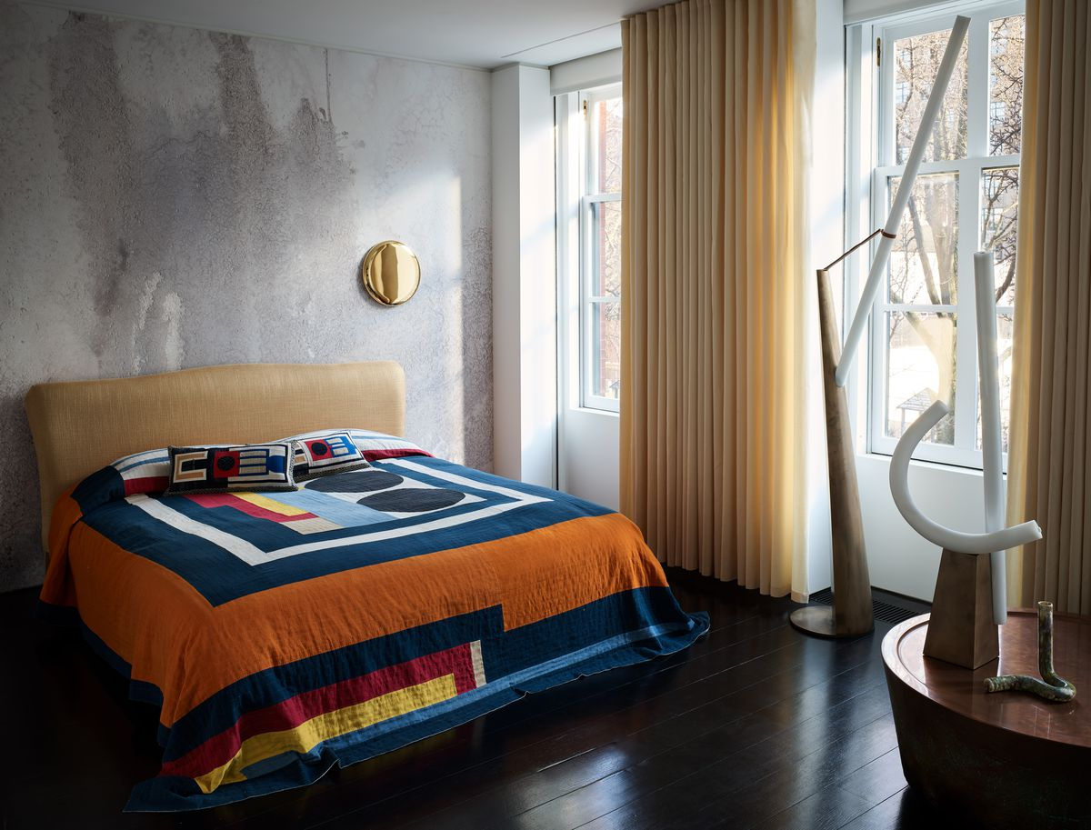A bedroom with a bed that has a multicolor patterned quilt and a gold colored headboard. The wall is concrete and there are floor to ceiling windows on one wall with gold drapes.