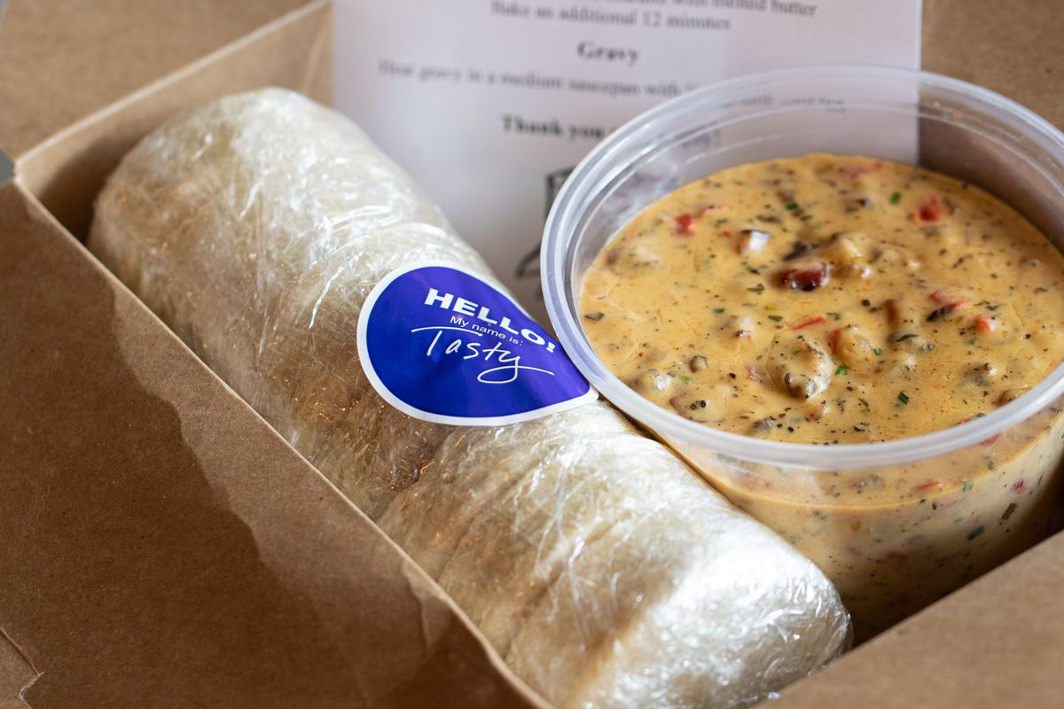 A plastic-wrapped roll of biscuits sits in a brown box next to a quart container of gravy. Behind it, a Tasty n Alder-branded paper includes instructions for how to prepare the dish