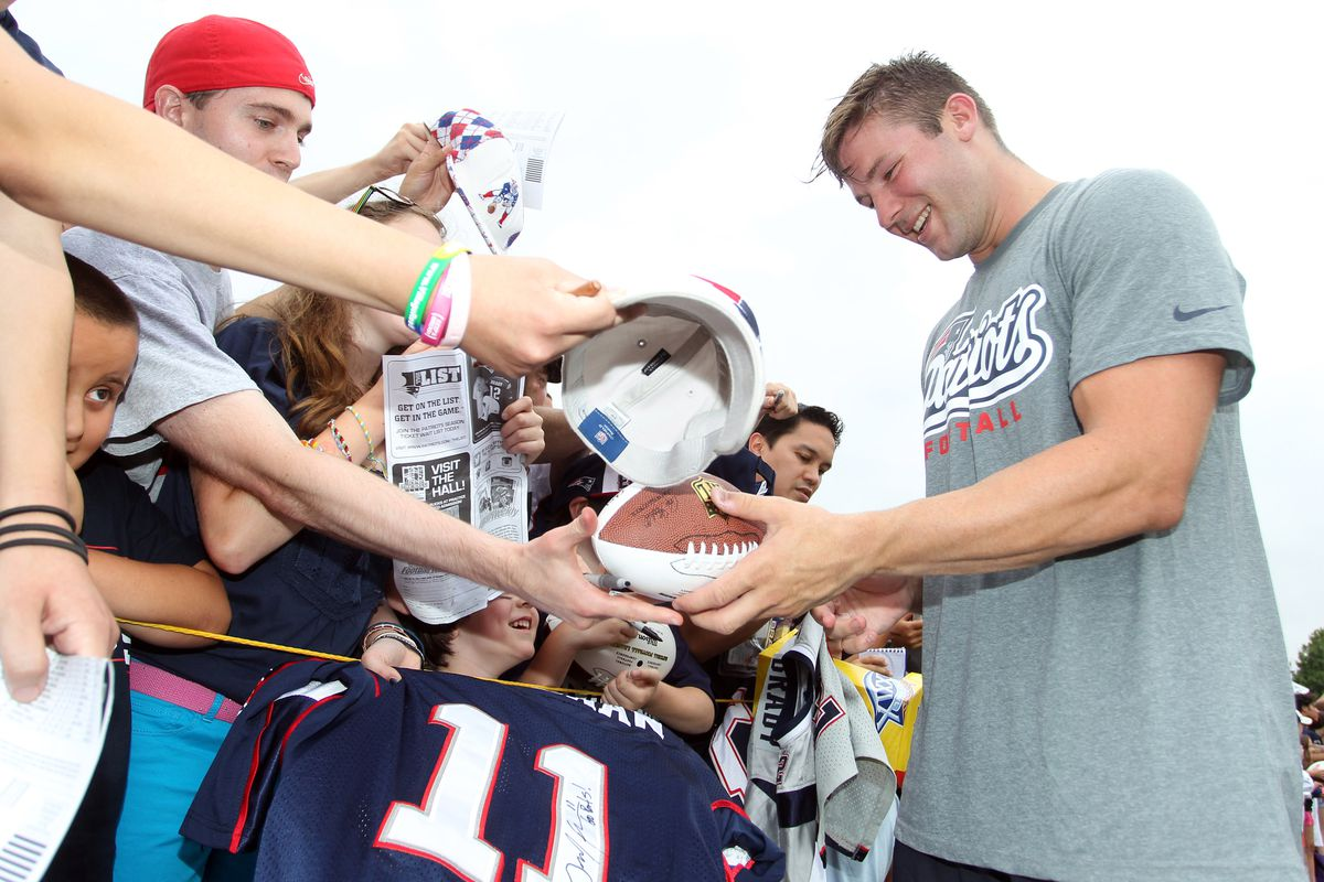July 27, 2012; Foxborough, MA, USA; New England Patriots wide receiver Julian Edelman (right) signs autographs during training camp at the team practice facility. Mandatory Credit: Stew Milne-US PRESSWIRE