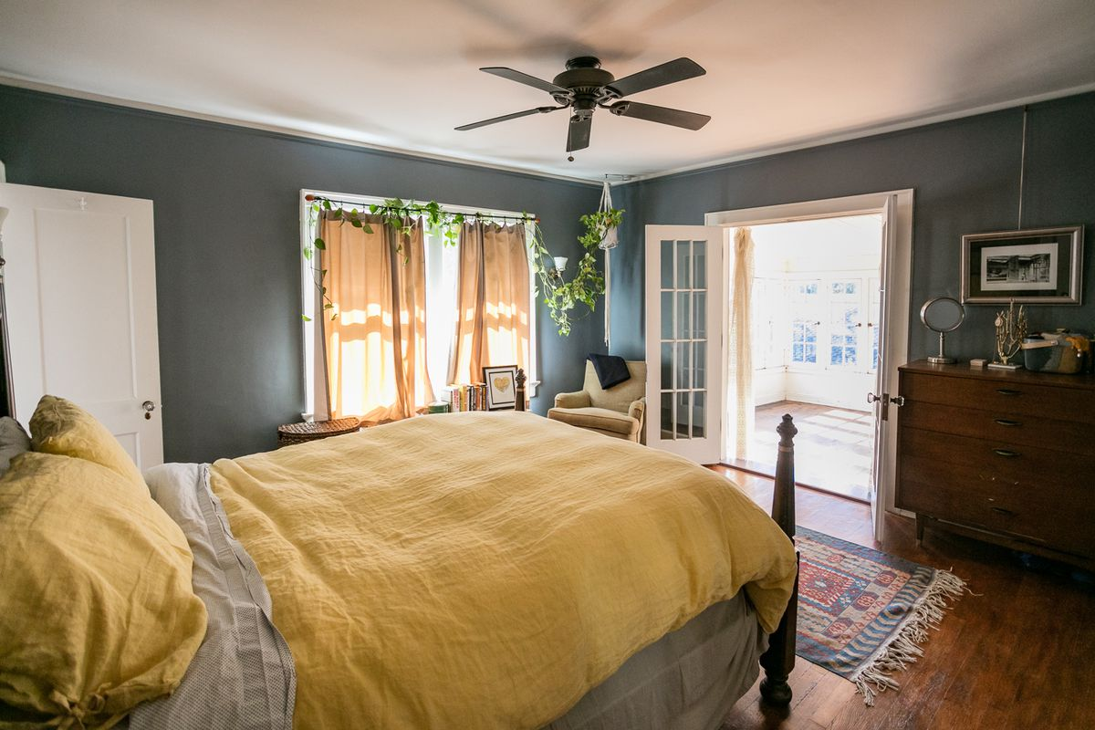 A bedroom with a bed and yellow sheets. The walls are painted dark brown and there's some yellow drapes over a window. Open doors across the bed lead to a bright sunroom.