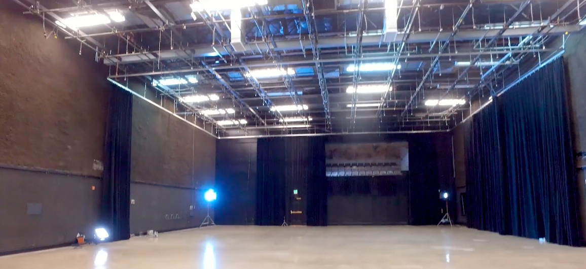 A large soundstage with brick wall and rigging overhead.