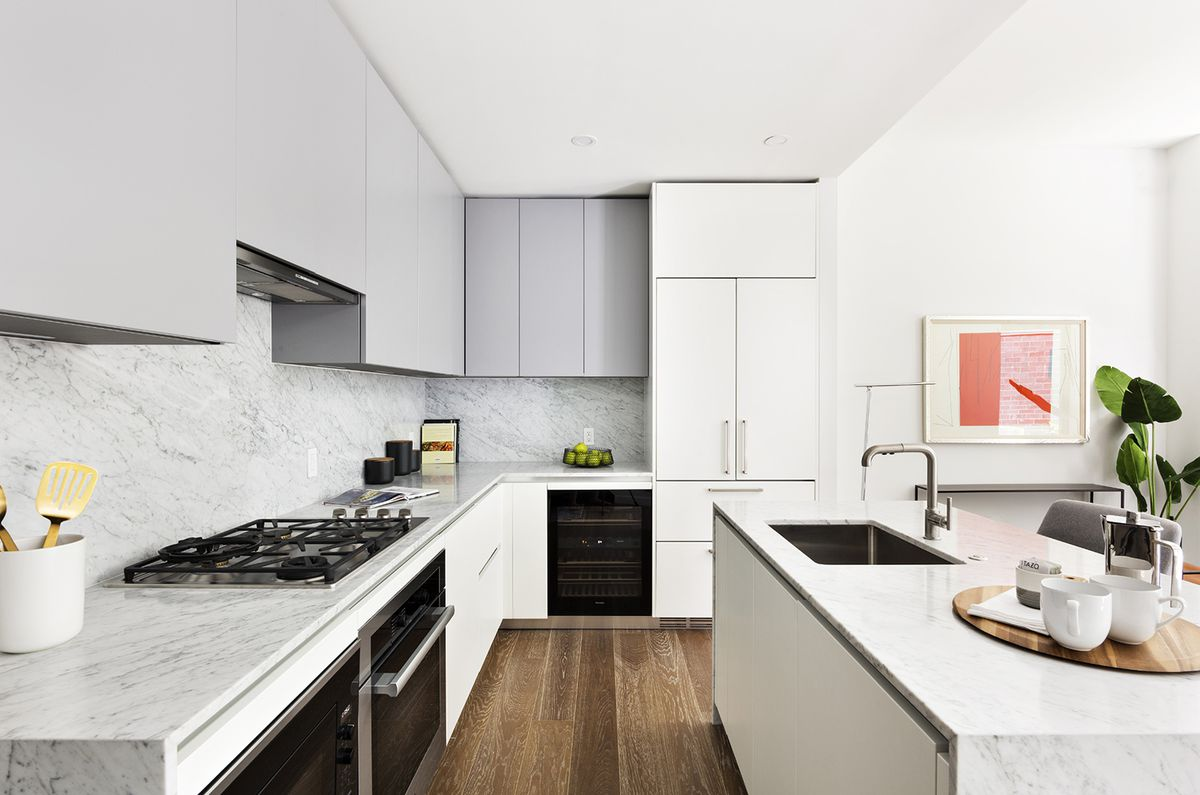 A kitchen with grey and white cabinetry.