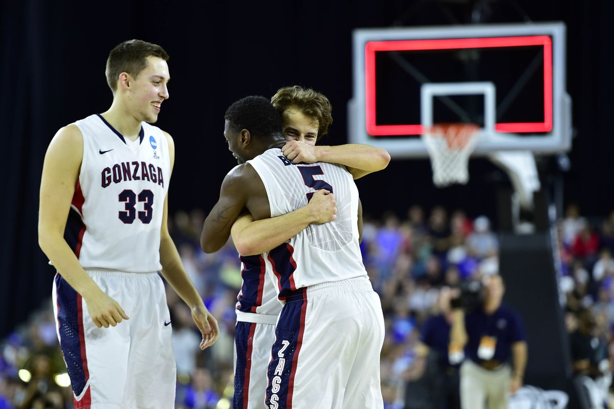 Gonzaga's Kyle Wiltjer (33) watches as seniors Kevin Pangos (4) and Gary Bell Jr. (5) hug after defeating the UCLA Bruins in the Sweet 16.