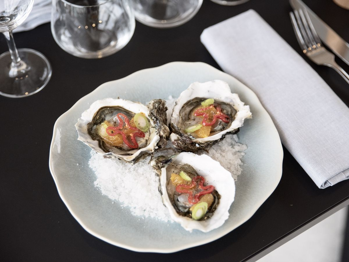 Three oysters sit on a bed of salt on a plate next to table settings