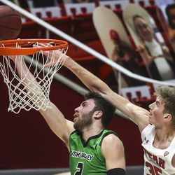 UVU Wolverines forward Evan Cole (2) gets past Utah Utes center Branden Carlson (35) for a basket during a game at the Huntsman Center in Salt Lake City on Tuesday, Dec. 15, 2020.