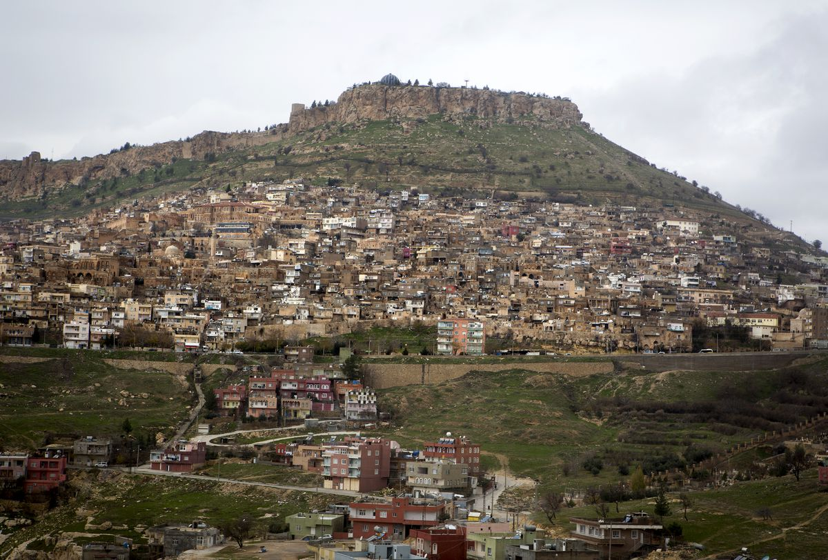 A city covers a hill in the distance
