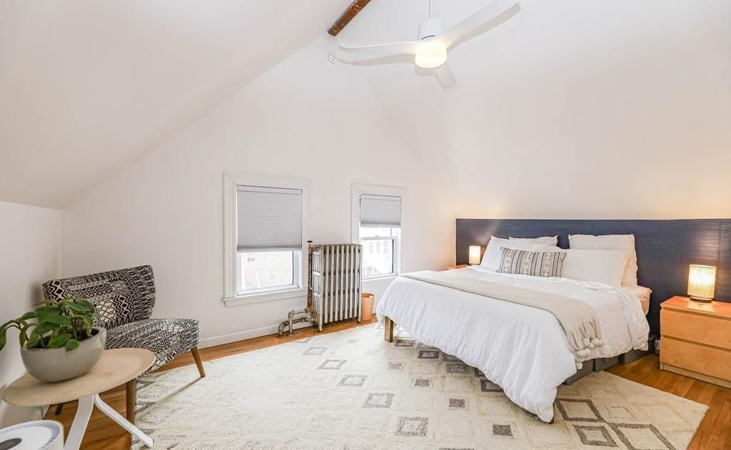 A bedroom with a bed, a peaked ceiling, and a radiator.