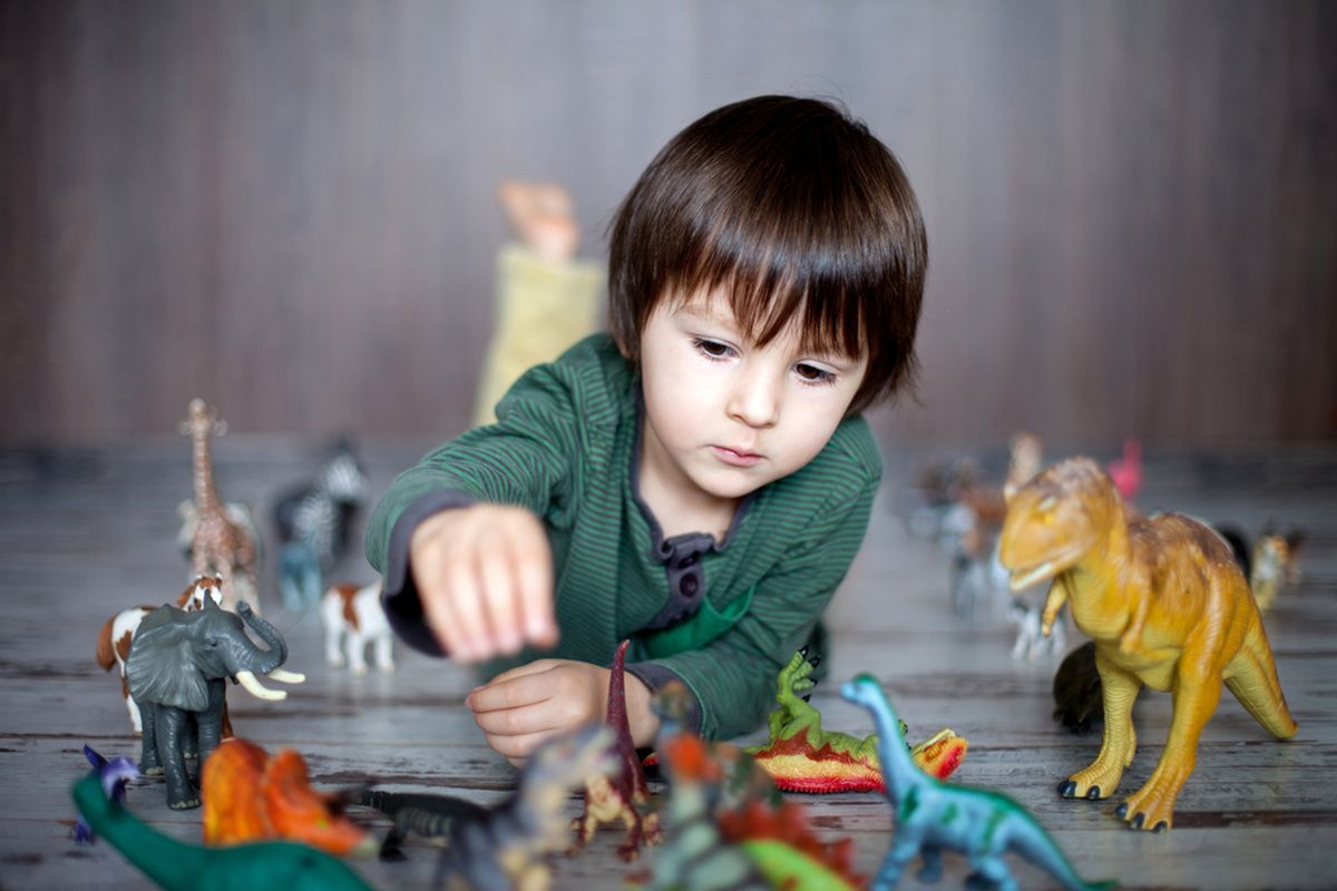 This is not the kid the critic interviewed, but it IS a kid playing with dinosaurs.