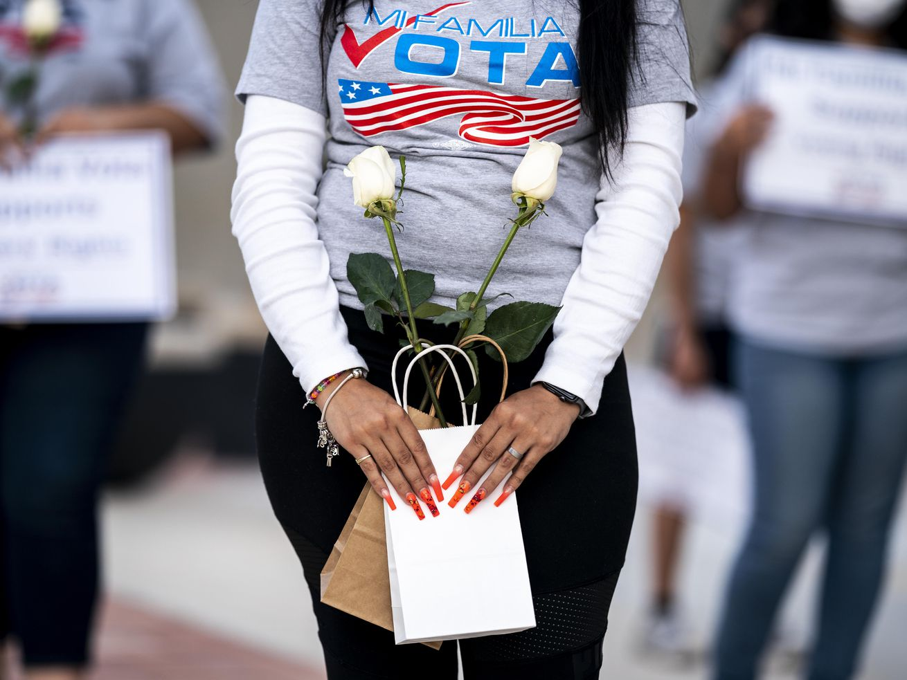 "A Latina woman wearing a shirt that reads ""Mi Familia Vota"" and carrying two small bags with a white long-stem rose in each."