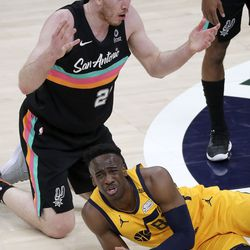 San Antonio Spurs center Jakob Poeltl (25) and Utah Jazz guard Miye Oni (81) react after losing possession of the ball they were fighting for during an NBA game at Vivint Smart Home Arena in Salt Lake City on Monday, May 3, 2021. The Jazz won 110-99.