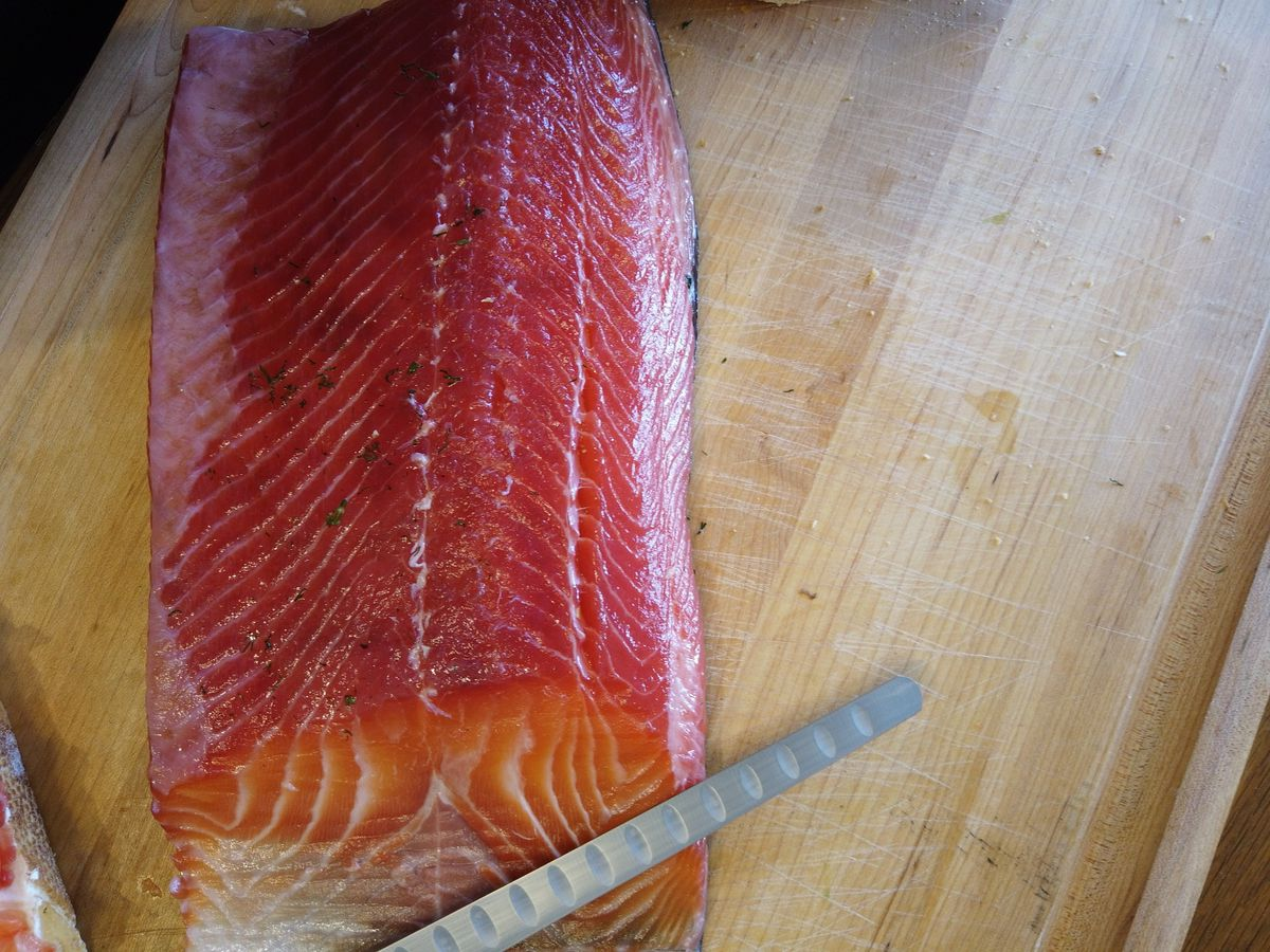 A slab of red, raw salmon rests on a counter beside a thin knife for cutting slices of lox