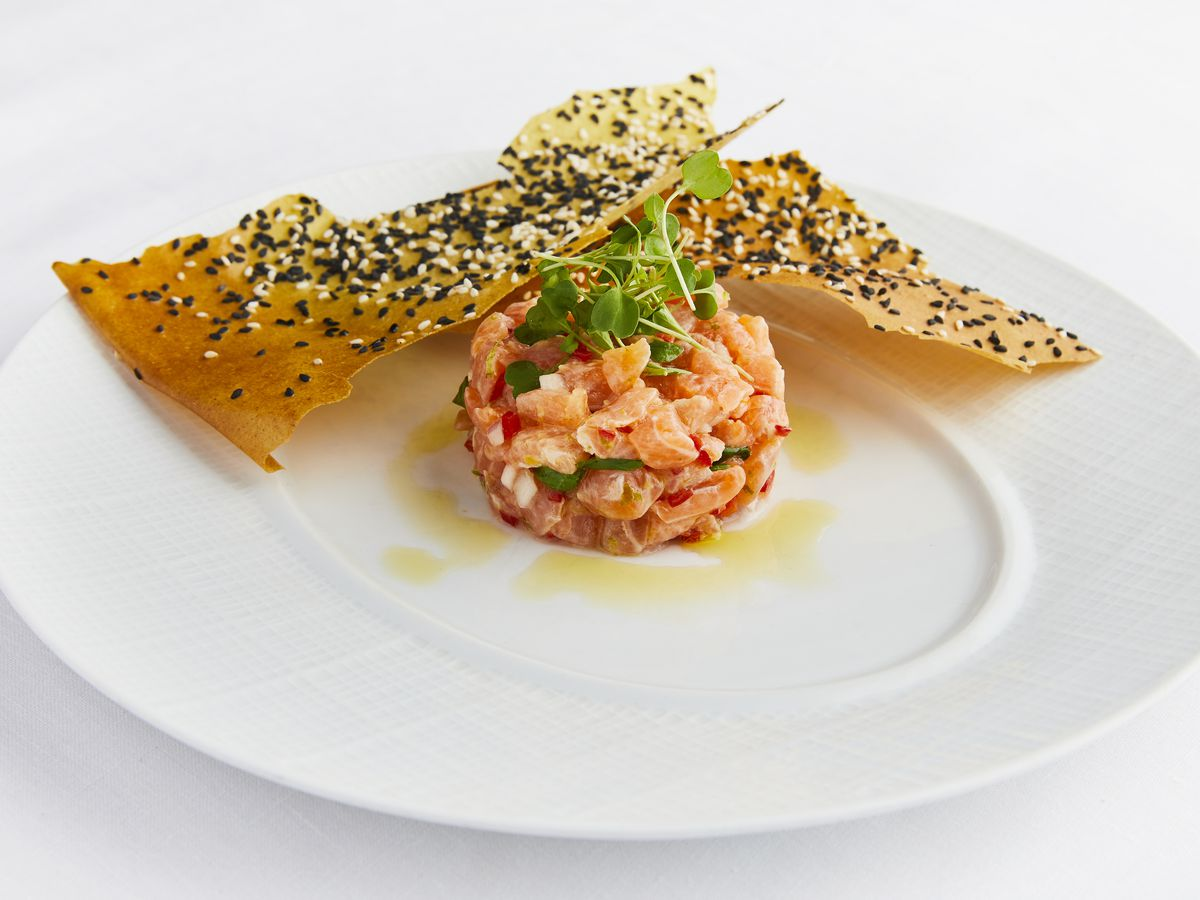A white plate with salmon tartare in a circle
