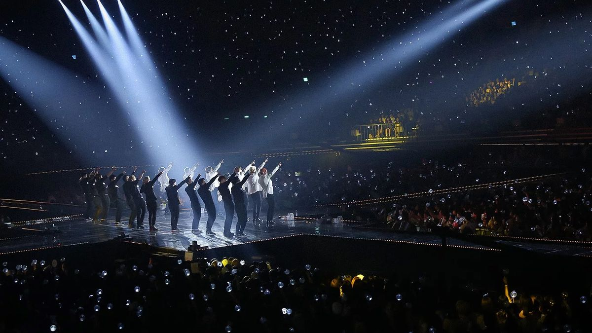 Dancers on a stage are lit by spotlights and surrounded by an arena of spectators.