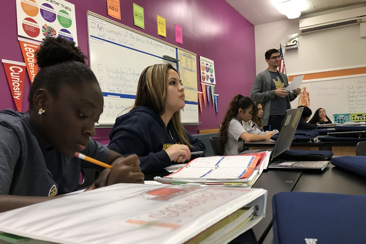 """Six students at Kepner Beacon Middle School sit at long tables and work on an assignment. One girl holds a pencil. A male teacher stands in the background. Behind them is a purple wall with banners saying 'Curiosity"""" and """"Leadership,"""" a whiteboard, and a poster listing character traits."""