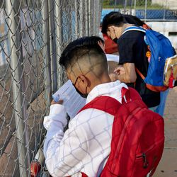 Pan American High School students complete their COVID screening forms against the fence at the school's entrance.