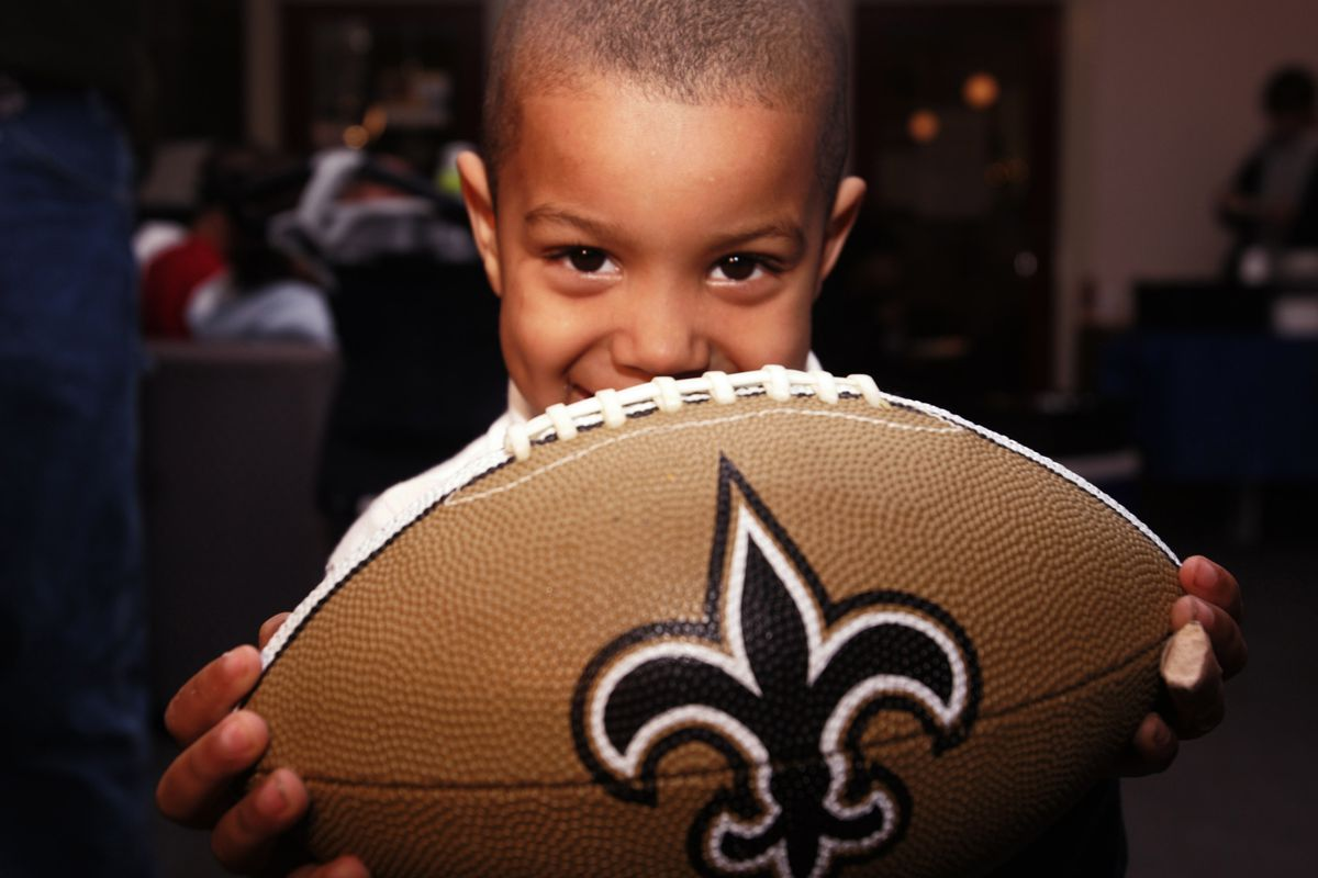 NEW ORLEANS, LA - A young Saints fan poses for a photo during the 2006 eBay Holiday Dreams Meet and Greet with Saints quarterback Drew Brees (not pictured) at the Covenant House.