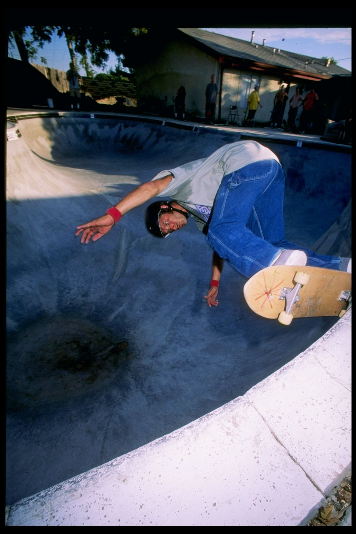 A grainy archival image of Tony Alva, dressed in blue jeans and an oversized gray t-shirt, skateboarding in a drained pool.