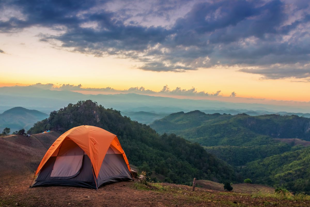 An orange tent on a mountain top. In the distance are mountains. There is a sunset and the sky is orange and purple.