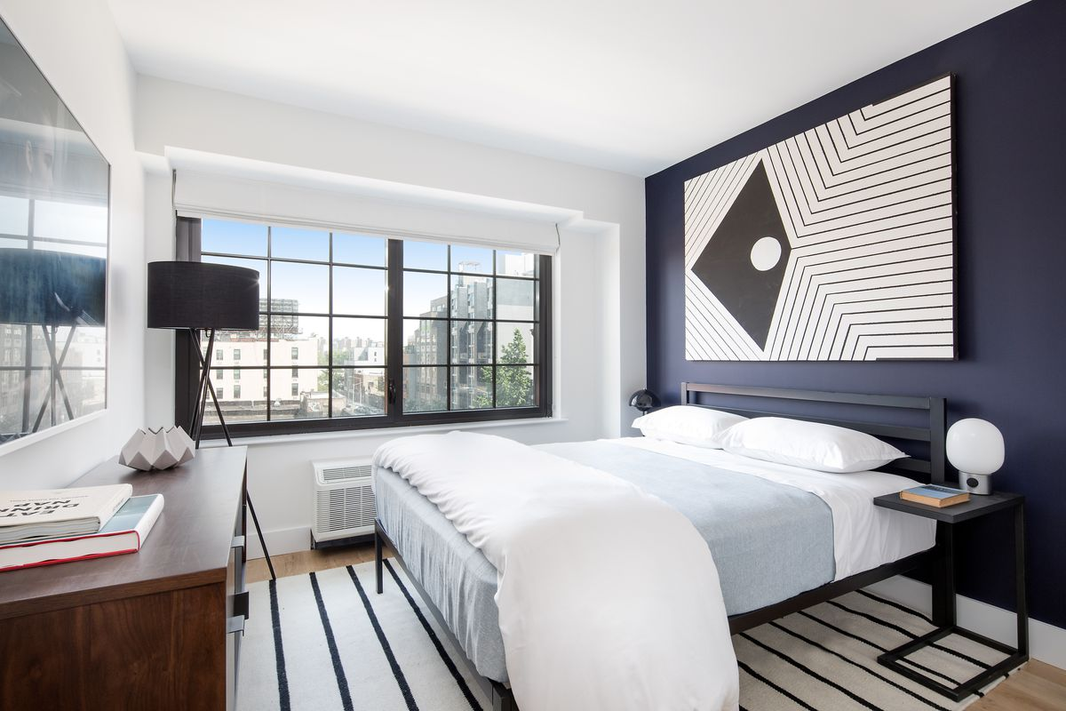 A bedroom with a large bed, a dark blue wall, a rug, and a large window.