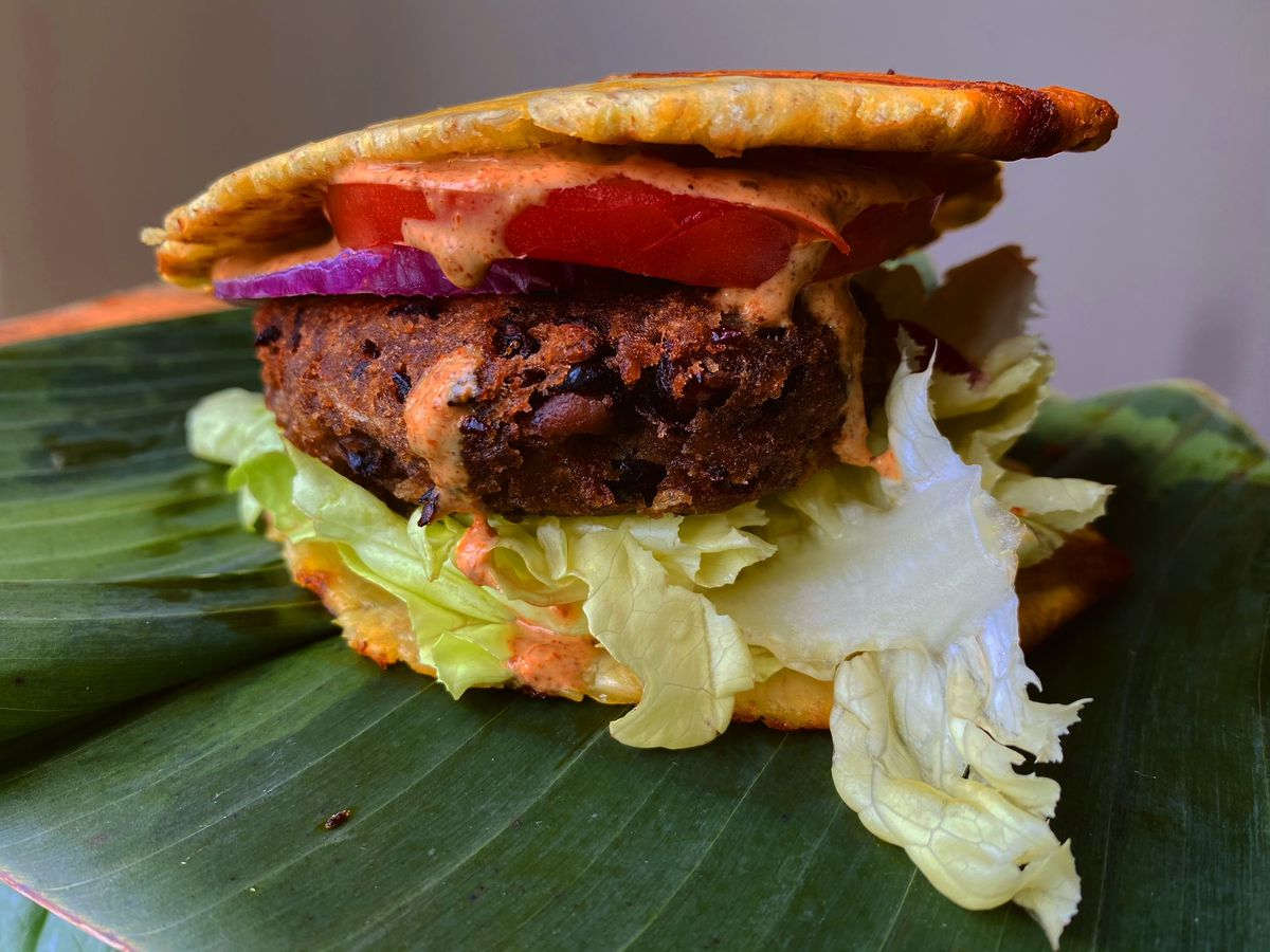 A burger with red tomato, purple red onion, and light green lettuce on a thin brown bun, sitting on a green banana leaf