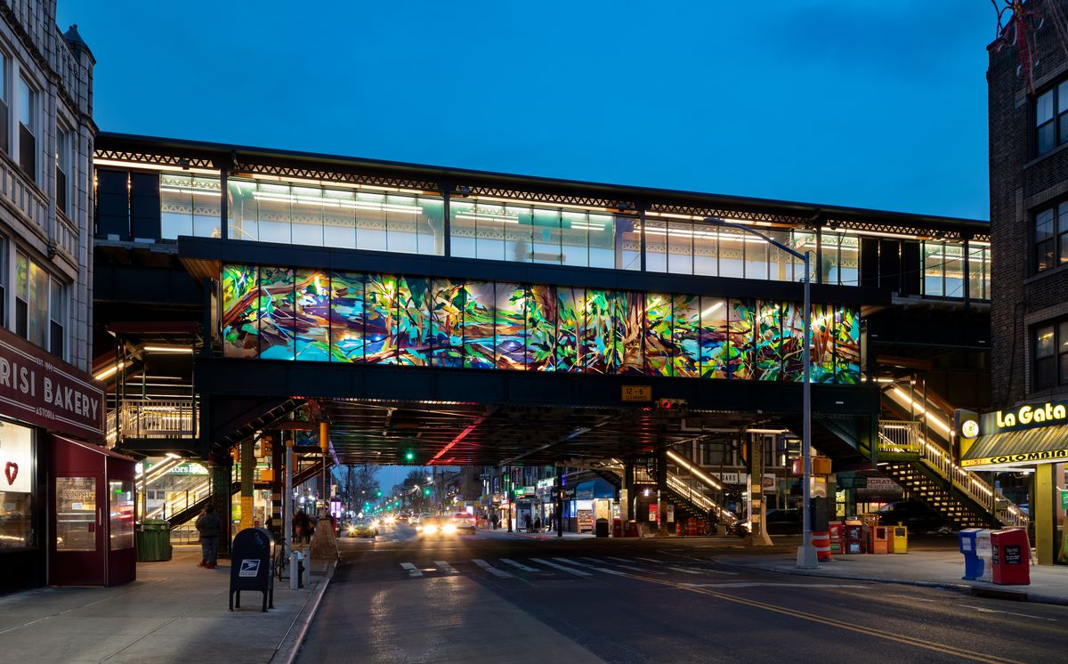 At dusk, a subway platform goes over a New York City street. An illuminated art piece travels the horizontal space over the bridge, filled with bright colors of blues, greens, and more.