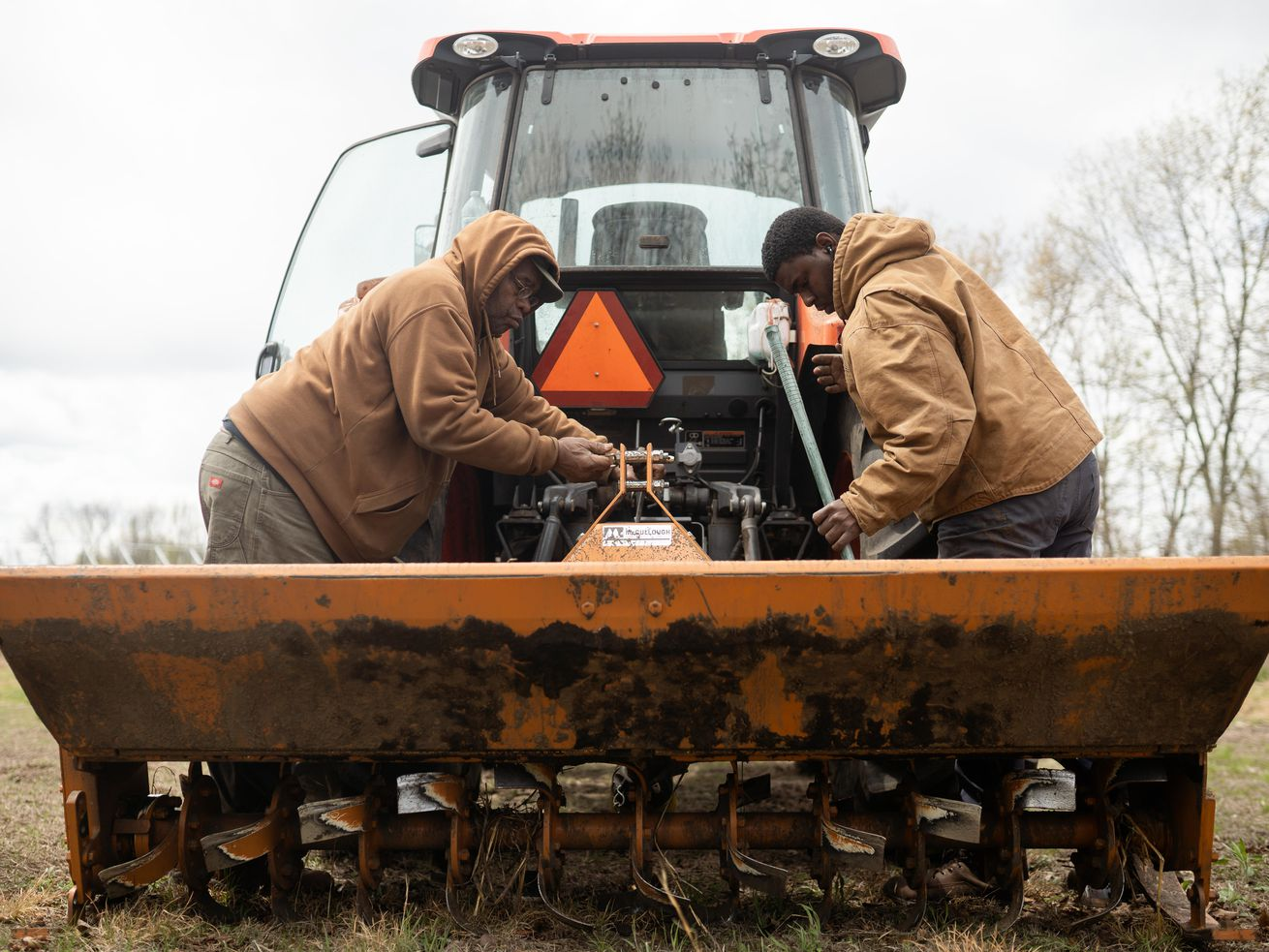 Akin Carter and his father Fred work on a tractor on their farm in Pembroke Township.