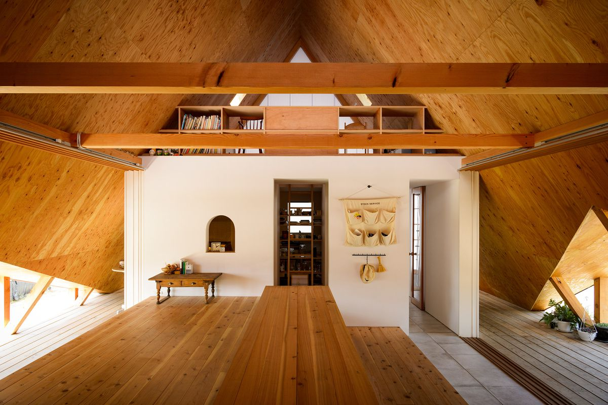 Steep, pointed ceiling clad in wood.