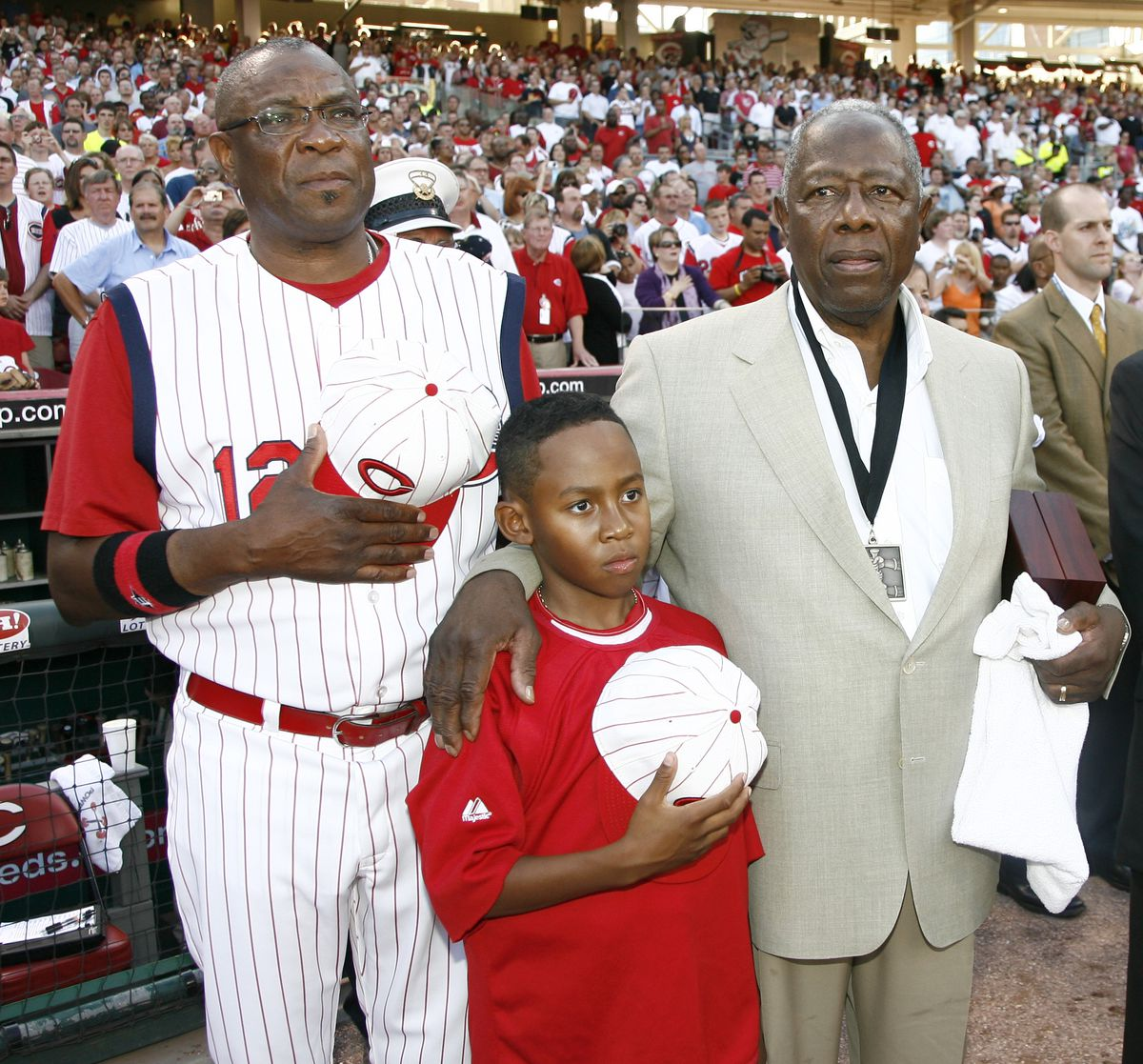 In this 2009 file photo, Reds manager Dusty Baker, left, stands with his son Darren Baker, center, and baseball legend and close friend Hank Aaron, right, as the national anthem plays at Great American Ball Park in Cincinnati.