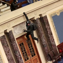 A protester is seen hanging from the balcony in the Senate Chamber on January 06, 2021 in Washington, DC. Congress held a joint session today to ratify President-elect Joe Biden's 306-232 Electoral College win over President Donald Trump. Pro-Trump protesters have entered the U.S.