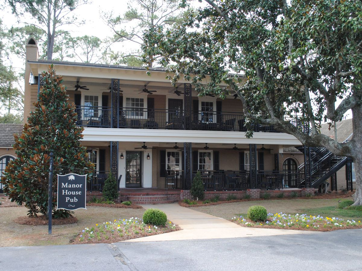 The exterior of a house with two stories and a white awning. There is a dark blue sign outside of the house with words which read: Manor House Pub.