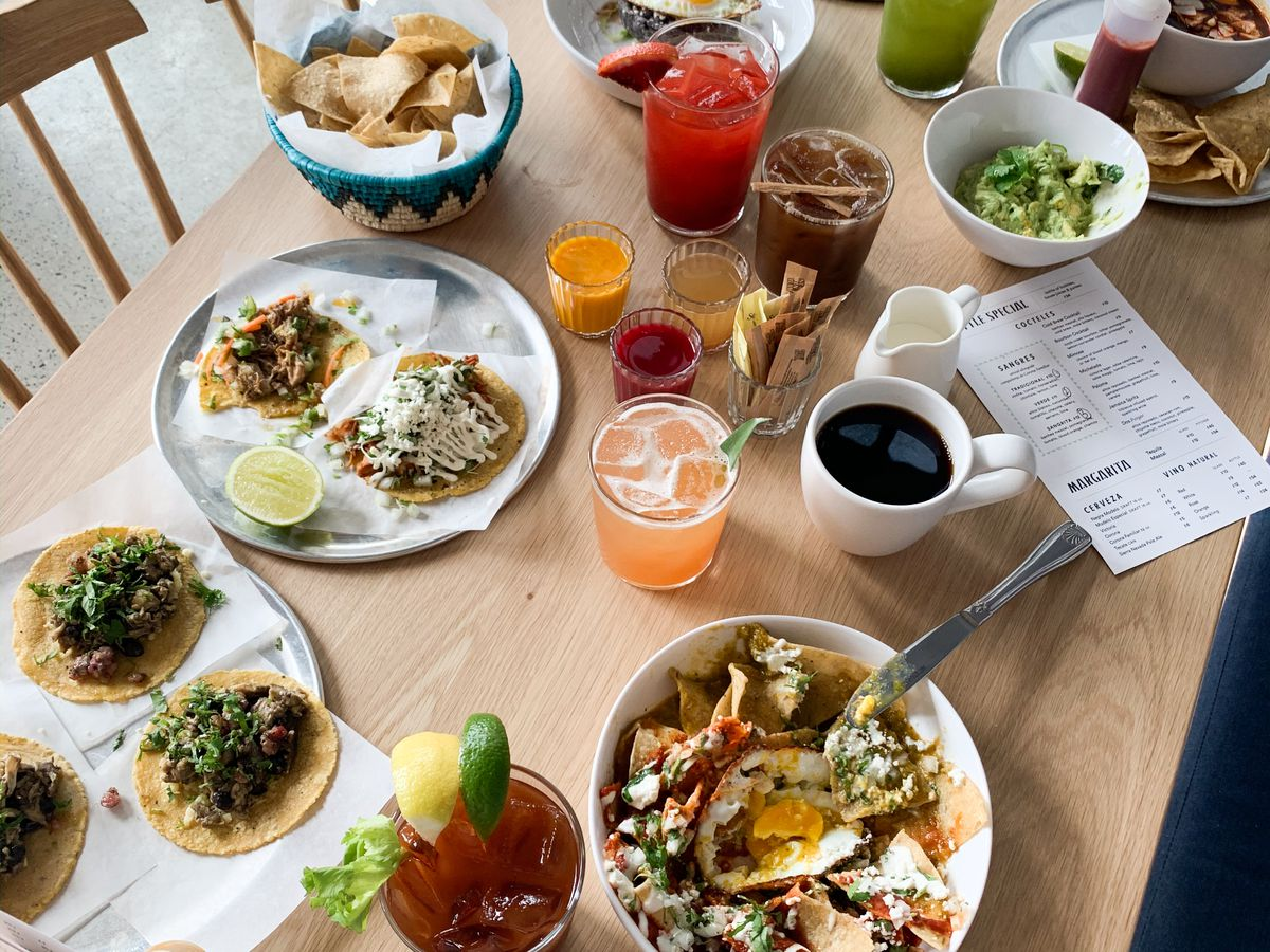 table covered with mexican dishes including tacos
