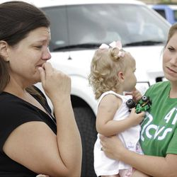 Misty Jones, left, mother of Abigail, center, fights back emotions Wednesday, April 4, 2012, as she talks about discovering that the home of her daughter's babysitter was struck by a tornado Tuesday, in Forney, Texas.  Jones' sister-in-law Jennifer Steed, right, watches as she tells of how Abigail was pulled from the rubble of the completely destroyed home.  (AP Photo/Tony Gutierrez)